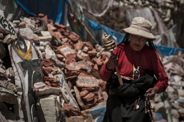 Mulher fazendo ora̵̤es ao redor de templo de pedras. Yushu РQinghai