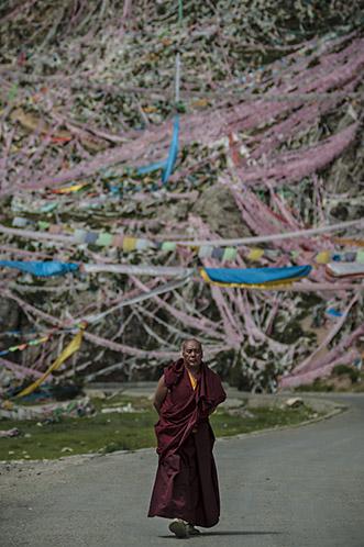 Monge budista com fl̢mulas ao fundo. Yushu РQinghai